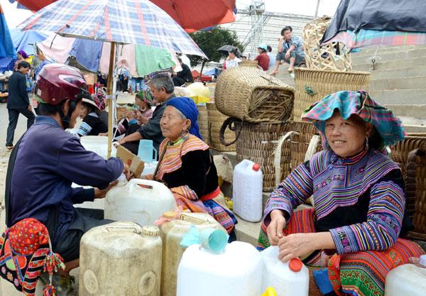 Bà con bán rượu ngô rất đông trong phiên chợ vùng cao với giá bán rượu ngô khác nhau